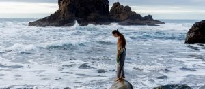 lonely woman standing at the rock waiting for her boyfriend to come back